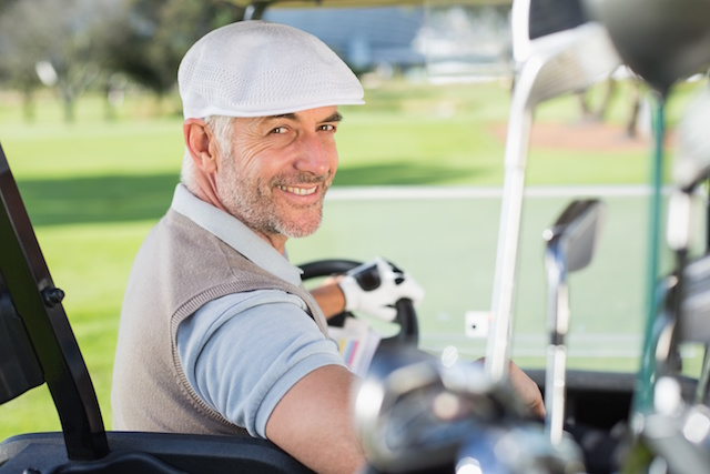 Happy golfer driving his golf buggy smiling at camera
